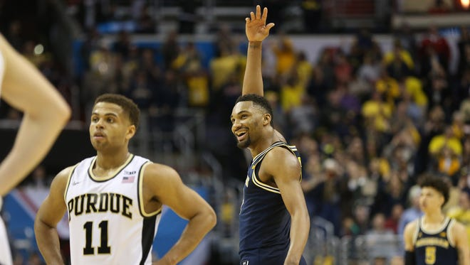 Michigan Wolverines guard Zak Irvin (21) celebrates after the game as Purdue Boilermakers guard P.J. Thompson (11) looks on during the Big Ten Tournament at Verizon Center. The Wolverines won 74-70 in overtime.