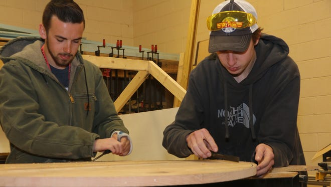 Chris Russell and Camden Smith have been working on their carpentry skills by building a table as part of the carpentry and construction program at Oakland High School.