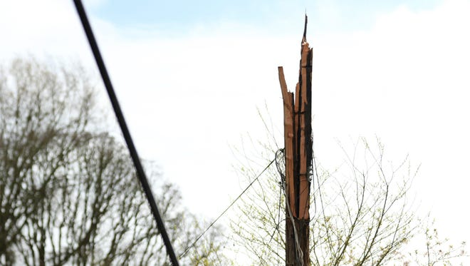 A power pole is broken as crews work to clean up a fallen cedar tree and downed power line at Parkway Drive and Bonnie Way NW following a wind storm in West Salem on Friday, April 7, 2017. The National Weather Service has issued a wind advisory until 5 p.m., gusts between 35 and 45 mph possible.