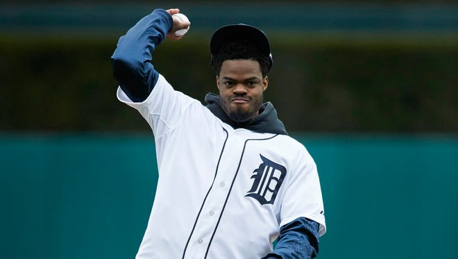 Apr 13, 2017; Detroit, MI, USA; Michigan Wolverines basketball player Derrick Walton Jr. throws out the ceremonial first pitch prior to the game between the Detroit Tigers and the Minnesota Twins at Comerica Park.