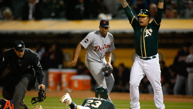 Athletics rightfielder Matt Joyce (23) slides as catcher Bruce Maxwell (13) begins to celebrate during the ninth inning of the Tigers' 6-5 loss Saturday in Oakland, Calif.