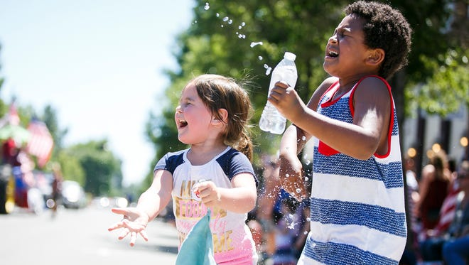 Lillian Evans, left, and Collin Mannen, right, cool off with a stream of water at the Fourth of July Grand Parade on Tuesday, July 4, 2017, in Independence. The parade started at Western Oregon University in Monmouth and made its way to Riverfront Park in Independence.