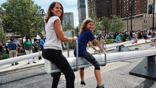 Mother and daughter, Lisa Muschong and Mya Muschong, use a giant seesaw at Beacon Park on Thursday, July 20, 2017 in Detroit.