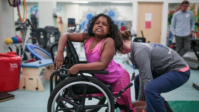 India Williams, 10, of Detroit struggles to get into her wheelchair by herself, while doing an exercise during therapy at the Children's Hospital of Michigan Specialty Center-Detroit on Wednesday May 31, 2017.