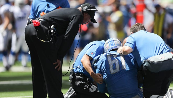 Lions coach Jim Caldwell checks on defensive lineman Kerry Hyder Jr., who was hurt during second quarter of the Lions' 24-10 win in the preseason over the Colts on Sunday, Aug. 13, 2017, in Indianapolis.