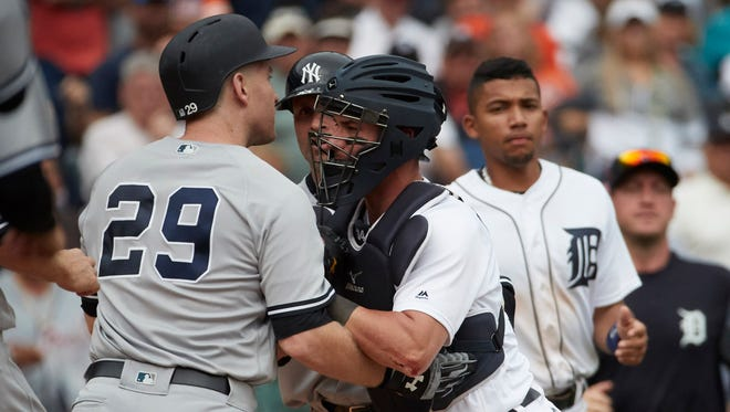 Tigers catcher James McCann (34) prevents Yankees third baseman Todd Frazier (29) from advancing on pitcher Alex Wilson (not pictured) after he is hit by a pitch in the eighth inning of the Tigers' 10-6 win on Thursday, Aug. 24, 2017, at Comerica Park.