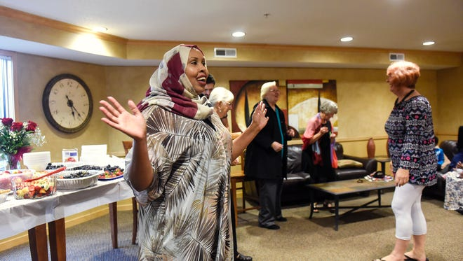 Hudda Ibrahim greets guests at the beginning of a Dine and Dialogue event Saturday, Aug. 26, in St. Cloud.