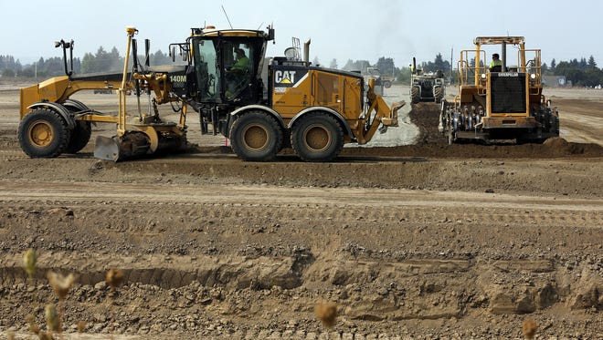 Workers drive construction vehicles over the site of a future Amazon packing and shipping center in Salem, Oregon, on Monday August 28, 2017.
