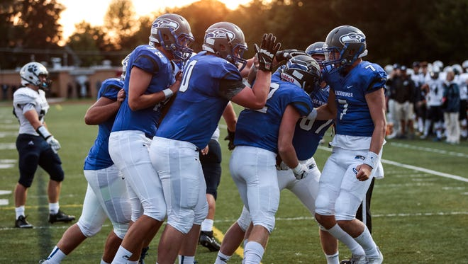 """Utica Eisenhower players celebrate a touchdown scored by  Caleb Oyster (32) in the second quarter against Macomb Dakota at Clinton """"Barney"""" Swinehart Field in Utica, Friday, Sept. 1, 2017."""