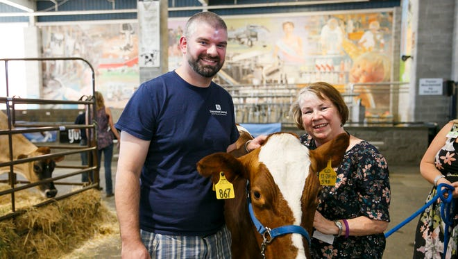 The Statesman Journal's Lee Clarkson and Carol Currie with 6-year-old milking shorthorn Ranger at the Oregon State Fair on Friday, Sept. 1, 2017, in Salem, Ore. Clarkson and Currie got a lesson in milking a cow from the Oregon Dairy Women.
