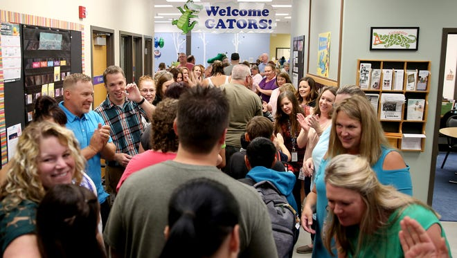 Teachers and staff welcome students during a red carpet welcome for back-to-school at Gubser Elementary School in Keizer on Wednesday, Sept. 6, 2017