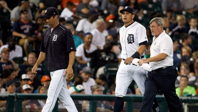 Sep 22, 2017; Detroit, MI, USA; Tigers' Mikie Mahtook walks off the field with manager Brad Ausmus (left) and trainer Kevin Rand after getting injured in the fourth inning against the Twins at Comerica Park.
