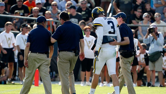 Sep 23, 2017; West Lafayette, IN, USA; Quarterback Wilton Speight walks off the field with Michigan trainers after an injury in the first quarter against Purdue at Ross-Ade Stadium.