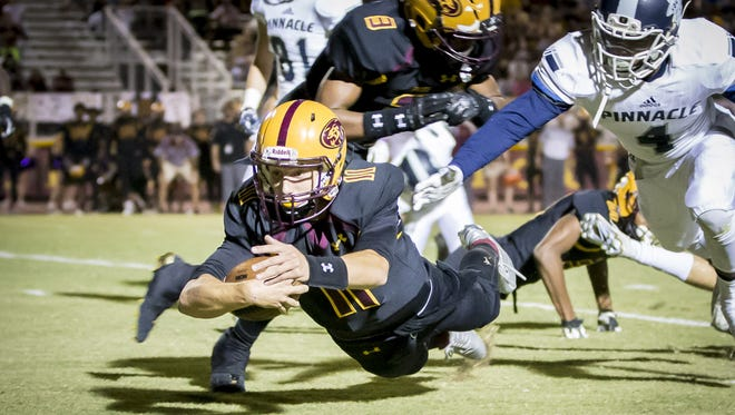 Quarterback Nick Wallerstedt of Mountain Pointe dives for yardage during the first half of the High School football game between Pinnacle and Mountain Pointe at Mountain Pointe High School on Friday, September 22, 2017 in Phoenix, Arizona.