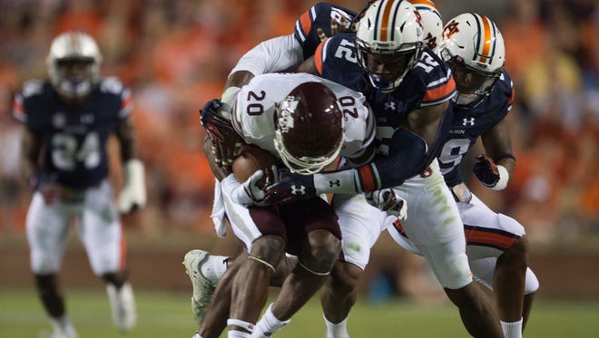 Auburn defensive back Jamel Dean (12) tackles Mississippi State wide receiver Reginald Todd (20) during the NCAA football game between Auburn and Mississippi State on Saturday, Sept. 30, 2017 in Auburn, Ala.