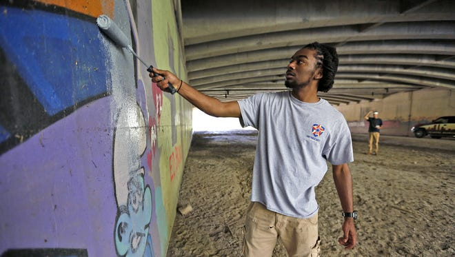 Kelsey Robinson, with the Indianapolis Graffiti Abatement Unit, paints over graffiti at an overpass along Fall Creek on the Fall Creek Greenway, Tuesday, Sept. 26, 2017.