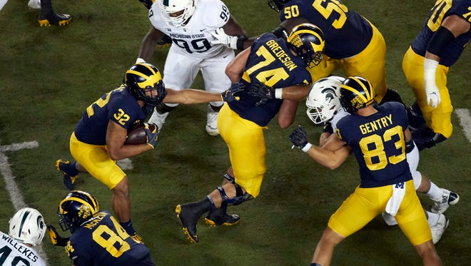 Michigan RB Ty Isaac (32) follows OL Ben Bredeson (74) in the first half against Michigan State at Michigan Stadium in Ann Arbor on Sat., Oct. 7, 2017.