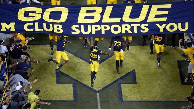 The Michigan Wolverines enter the field prior to the game against Michigan State at Michigan Stadium last season.