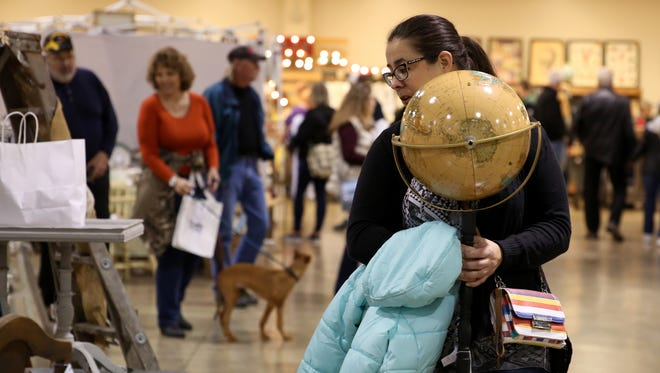 Candy Bigbee, of Marcola, Ore., carries globe she purchased at the Great Junk Hunt at the Oregon State Fairgrounds in Salem on Saturday, Oct. 21, 2017.