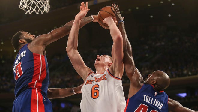 Pistons Andre Drummond, left, and Anthony Tolliver battle Knicks forward Kristaps Porzingis for a rebound on Saturday night in New York.