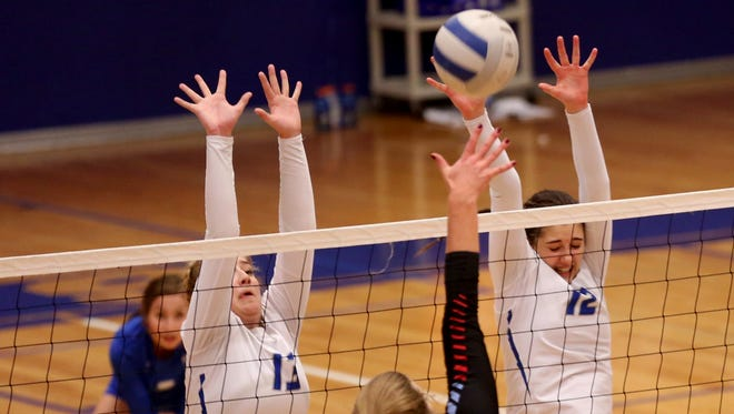 McNary's Kara Thomas (13) and Caiya Ewert (12) go up in the South Salem vs. McNary volleyball game at McNary High School in Keizer on Thursday, Oct. 19, 2017.