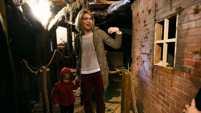 Chloe Larson explains some of the scenes constructed for a haunted house in Nicole Shuba's basement on Tuesday, Oct. 24, 2017. Shuba hired Larson to help design and construct the haunted house for her eleventh-annual Halloween party.