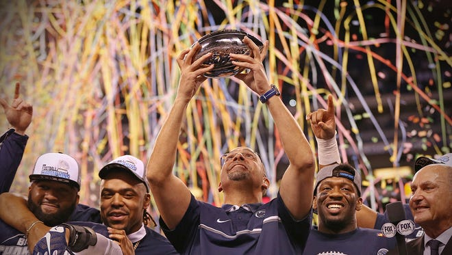 Penn State coach James Franklin holds up the Stagg championship trophy after winning the Big Ten championship at Lucas Oil Stadium, Oct. 3, 2016.