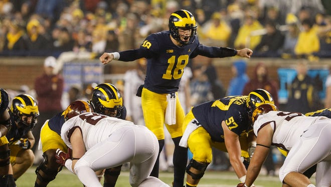 Michigan quarterback Brandon Peters (18) talks to teammates at the line of scrimmage before a play in the first half against Minnesota at Michigan Stadium in Ann Arbor, Saturday, Nov. 4, 2017.