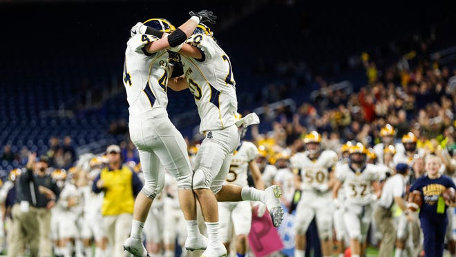 Clarkston players celebrate after an interception against West Bloomfield during the first half of the MHSAA Division 1 championship game at Ford Field in Detroit, Saturday, Nov. 25, 2017.