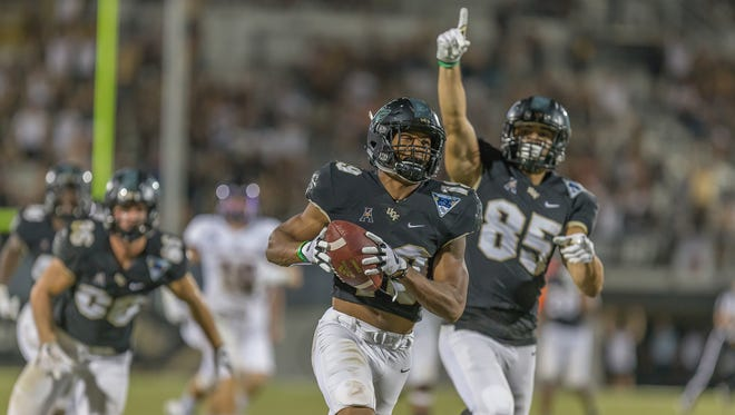 UCF's Mike Hughes runs a kickoff back for a touchdown to help seal UCF's victory over USF.