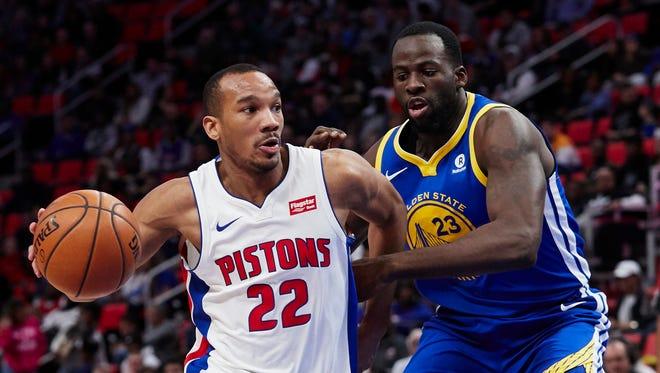 Dec 8, 2017; Detroit, MI, USA; Pistons guard Avery Bradley dribbles against Warriors forward Draymond Green in the second half at Little Caesars Arena.