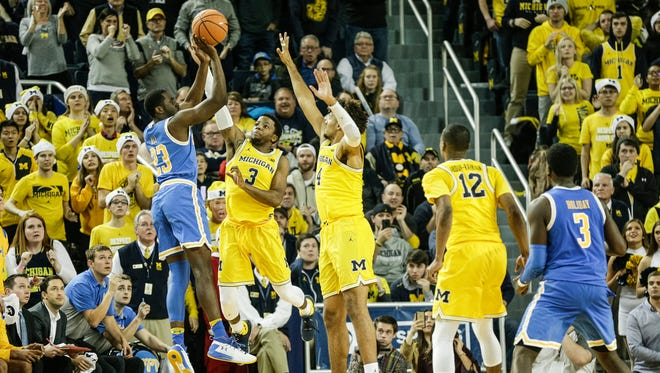 Michigan's Zavier Simpson (3) and Isaiah Livers try to block a shot from UCLA's Prince Ali during the second half at Crisler Center in Ann Arbor, Saturday, Dec. 9, 2017.