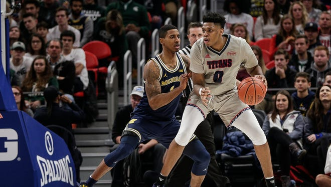 Detroit Mercy guard Kameron Chatman is defend by Michigan guard Charles Matthews during the second half of the Hitachi College Basketball Showcase at Little Caesars Arena in Detroit, Saturday, Dec. 16, 2017.