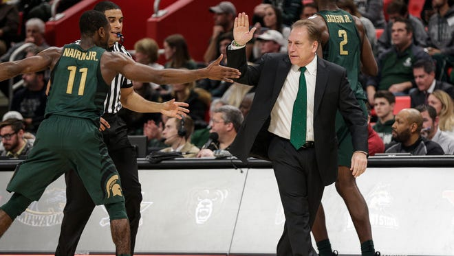 Michigan State coach Tom Izzo high fives Tum Tum Nairn Jr. in the second half of the Hitachi College Basketball Showcase against Oakland at Little Caesars Arena in Detroit, Saturday, Dec. 16, 2017.