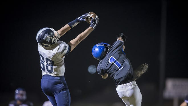 Wide receiver Hayden Hatten (88) of the Pinnacle Pioneers makes a catch against defensive back Randy Robinson (1) of the Chandler Wolves.