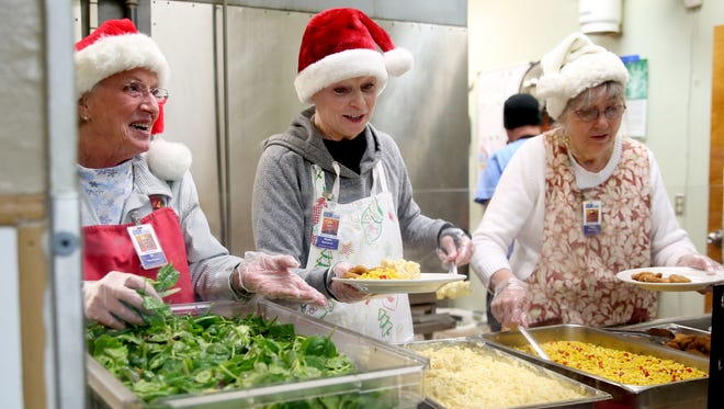 Jo Philippi, from left, of Mehama, Marlie Rowell, of Salem, and JoAnn Onstott, of Salem, serve lunch at the Union Gospel Mission in downtown Salem on Tuesday, Dec. 12, 2017. The trinity of volunteers have been serving lunch every Tuesday for about the last 13 years.