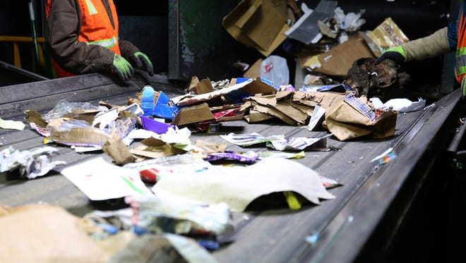 Sorters pull non-recyclables from a conveyor belt at Garten Services.