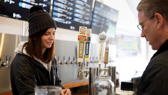 Volunteer bartender Katie Herber serves a customer at the Salem Winter Brewfest outside the Oregon State Capitol in Salem on Saturday, Feb. 3, 2018.