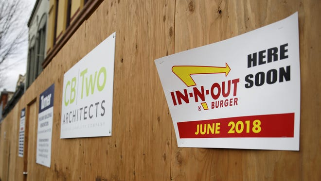 Signs claiming an In-N-Out is coming soon are posted outside the former location of The Brick in downtown Salem.