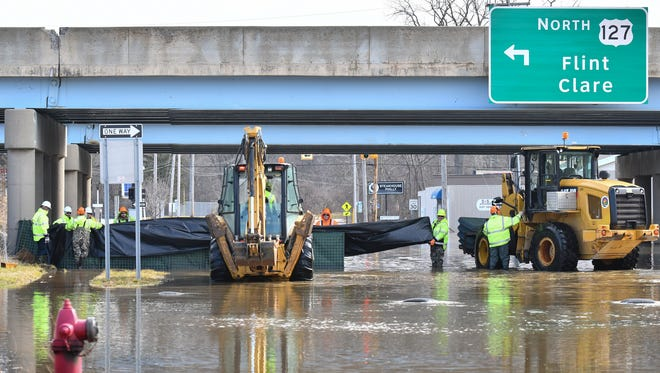 Work crews work to build a dam-like barrier, Thursday, Feb. 22, 2018, at Howard and Kalamazoo under the US-127 overpass.