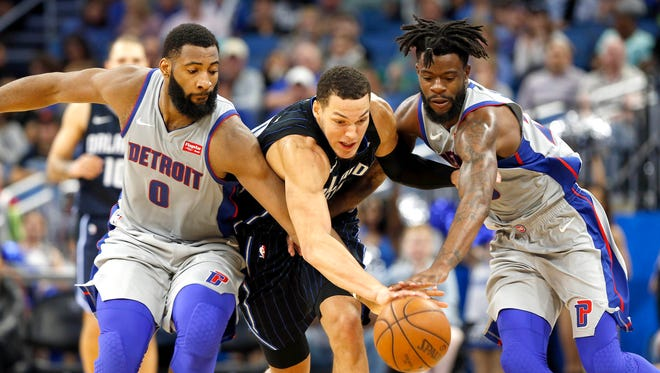Magic forward Aaron Gordon battles the Pistons' Andre Drummond and Reggie Bullock for the ball during overtime at Amway Center last season.