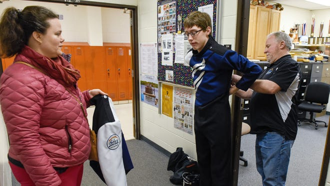 Jacob Starren, center, tries on the new Solar Sound marching band uniform Thursday, March 15, for uniform fitter Portia Hunstiger and Director Gary Zwack.