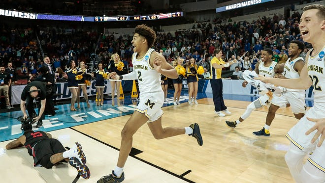 Michigan guard Jordan Poole celebrates after scoring a 3-pointer to defeat Houston in the second round of the NCAA tournament at INTRUST Bank Arena in Wichita, Kan., Saturday, March 17, 2018.