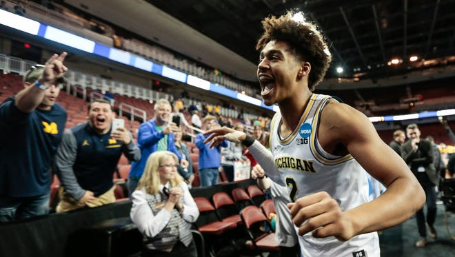 Jordan Poole celebrates with Michigan fans as he runs off the court, after his buzzer-beater defeated Houston, 64-63, in the second round of the NCAA tournament at INTRUST Bank Arena in Wichita, Kan., Saturday, March 17, 2018.