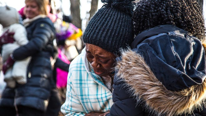 In this Sunday, March 11, 2018, photo, Najah Konney embraces another family after saying goodbye to her niece, Mujey Dumbuya, as family and friends gather at the site where Mujey's body was found in Kalamazoo, Mich. Mujey's family last saw her alive on Jan. 24 as she headed off to East Kentwood High School in Kentwood, near Grand Rapids. Passers-by found her body four days later in Kalamazoo.