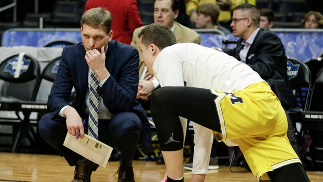 Michigan assistant Luke Yaklich talks to Duncan Robinson during warmups before the Elite Eight game against FSU on Saturday.