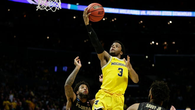 Michigan's Zavier Simpson makes a layup against Florida State's Phil Cofer (0) and PJ Savoy (5) during the second half of the Elite Eight in the NCAA tournament in Los Angeles, Saturday, March 24, 2018.