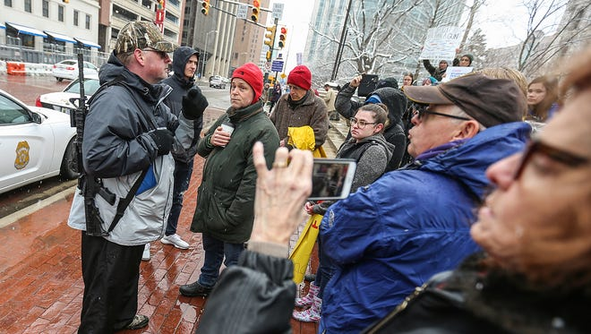 Attendees of the March for Our Lives rally in Indianapolis confronted a counter-protester who carried a rifle while they all waited outside the Indiana Statehouse on March 24, 2018. The man with the rifle withheld his name.