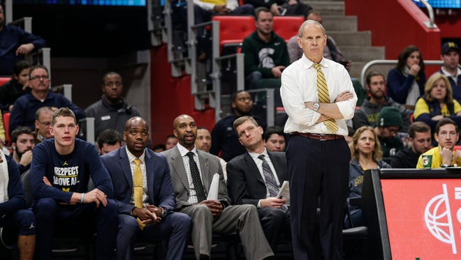 Michigan coach John Beilein, right, and (left to right) Michigan forward Moe Wagner, and assistant coaches DeAndre Haynes, Saddi Washington and Luke Yaklich, watch a play during the second half against Detroit Mercy at Little Caesars Arena in Detroit, Dec. 16, 2017.