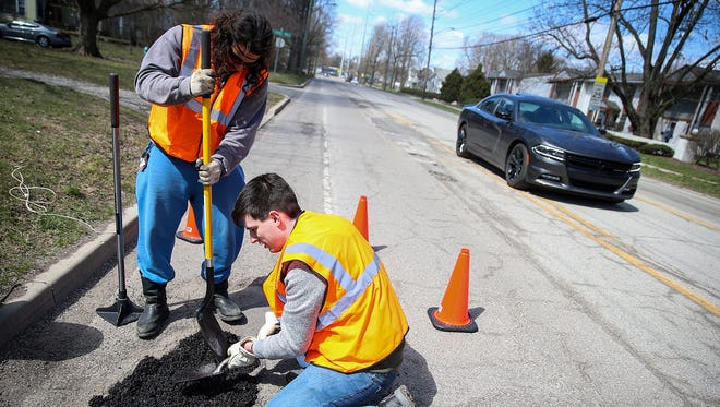 From left, Mike Warren and Chris Lang fill a pothole along 52nd Street at Haverford Avenue in Indianapolis, Saturday, April 7, 2018. The duo began Open Source Roads, a grassroots organization aimed at repairing Indiana's pothole-riddled roads. Warren and Lang feel the city is failing its residents in effectively repairing roads, putting drivers and cyclists at risk. They purchase the materials at local hardware stores, gather friends to volunteer and patch holes on Indy's worst side streets whenever time and resources allow.